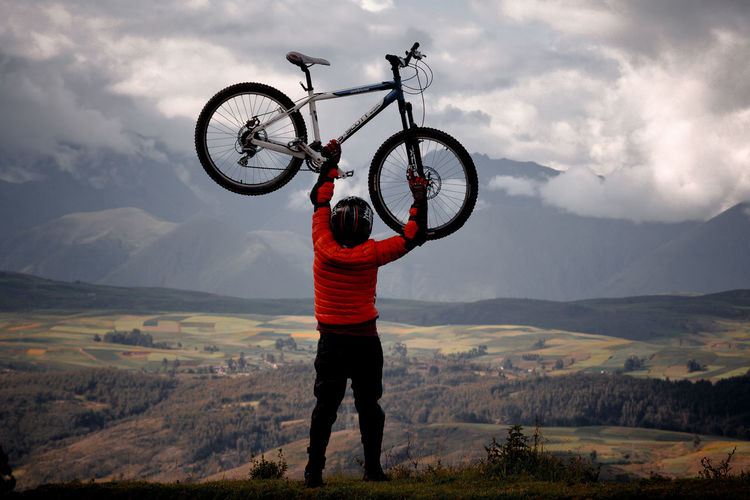 Man with bicycle standing on mountain against sky