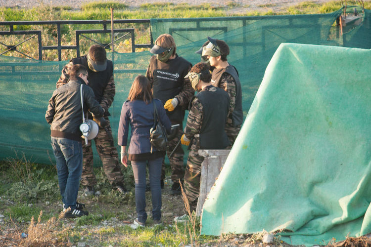 Paintball Players Preparing And Planning Game On Field