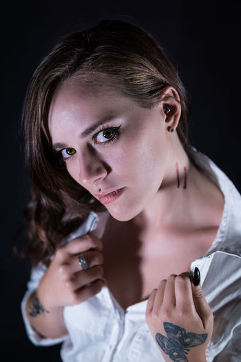 Portrait Of Young Woman Showing Wounds On Neck Against Black Background