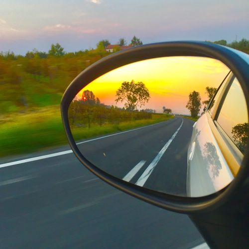 Road seen through side-view mirror of car