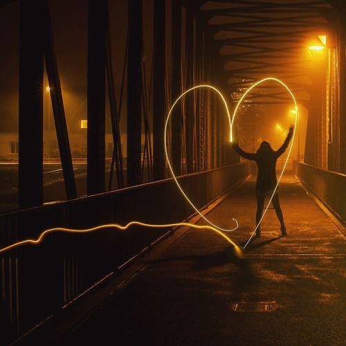 Woman Doing Light Painting On Heart Shape At Illuminated Bridge