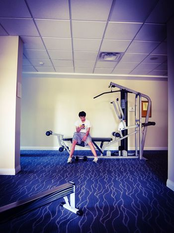 Taking a rest Resting Rest Fitness Workout Exercise Time Exercise Equipment Exercising Full Length One Person Indoors  Real People Adult Casual Clothing Sport Ceiling Front View Gym Wall - Building Feature