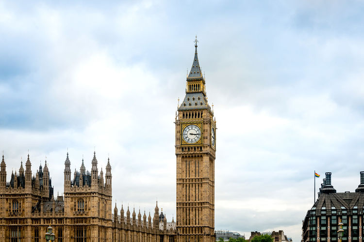 Low angle view of big ben in city against cloudy sky