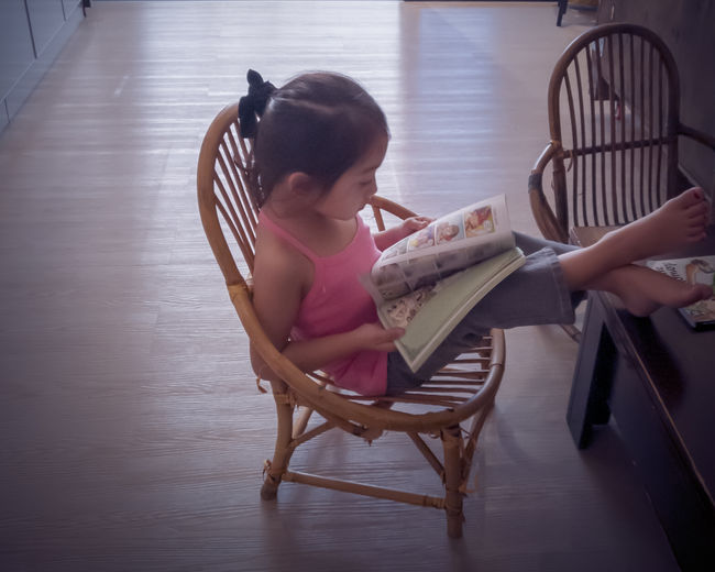 High angle view of girl sitting on chair at home
