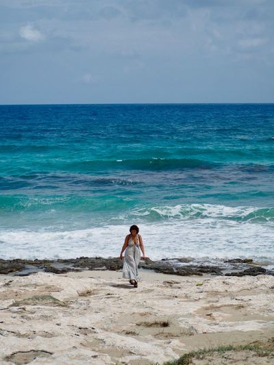 Full Length Of Woman Walking At Beach Against Sea And Sky