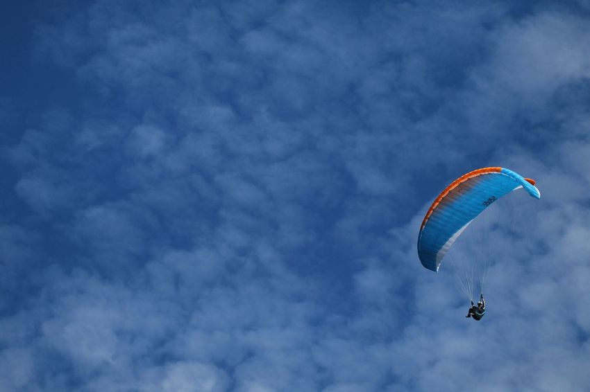 Flying Mid-air Extreme Sports Sky Paragliding Parachute Multi Colored Cloud - Sky Leisure Activity Motion Low Angle View Sport Outdoors People Day One Person Nature Vapor Trail Stunt Person Aerobatics Blue Sky