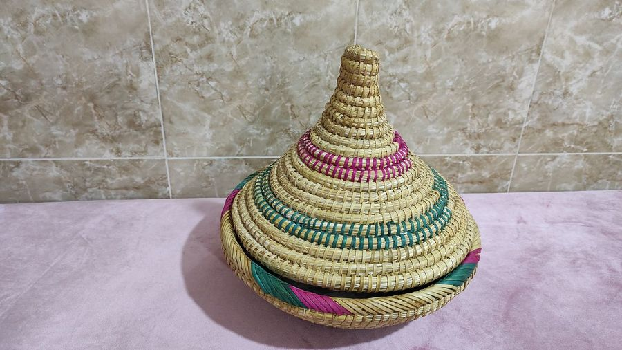 Close-up of hat on table against wall