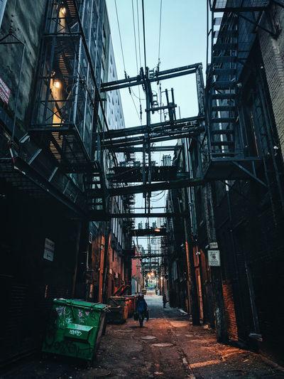 Man walking on narrow street amidst buildings in city