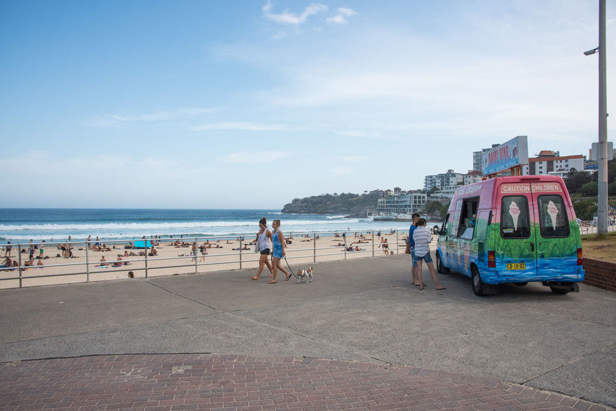 SYDNEY,NSW,AUSTRALIA-NOVEMBER 21,2016: Foreshore with tourists and ice-cream vendor at Bondi Beach in Sydney, Australia Australia Dessert Vacations Beach Bondi Break Day Dog Ice Cream Ice Cream Truck Indulgence Leisure Activity Nature Outdoors Pacific Ocean Pet Real People Sea Sky Sydney Treat Van Vendor Walking The Dog Water