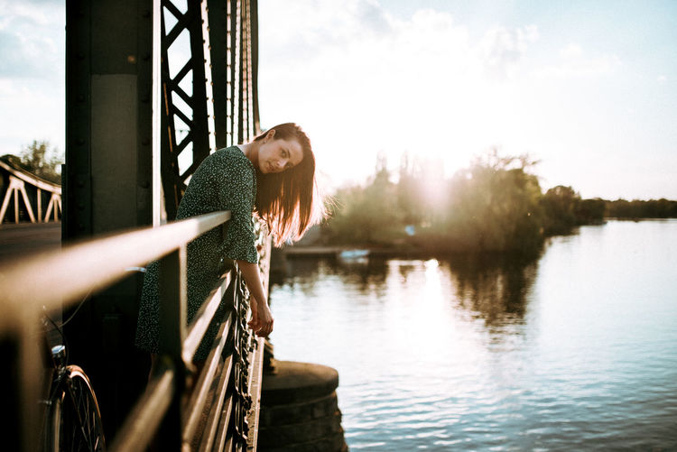 Woman standing by railing against lake