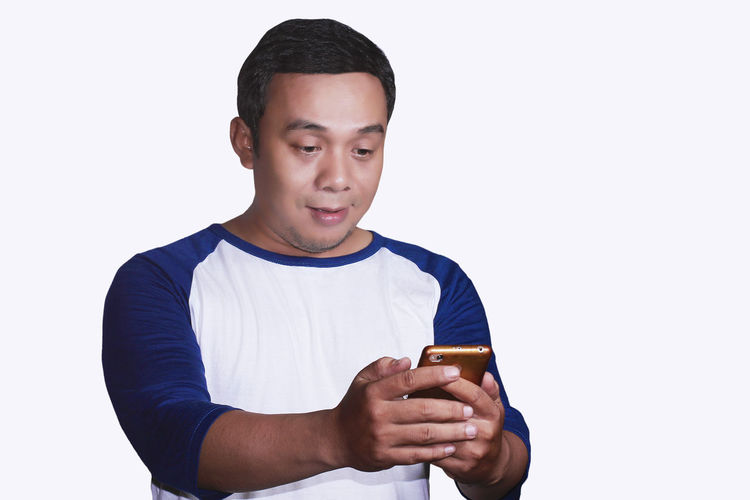 Portrait of a happy asian man with something on smartphone Casual Clothing Copy Space Holding Looking Males  One Person Portrait Standing Young Men