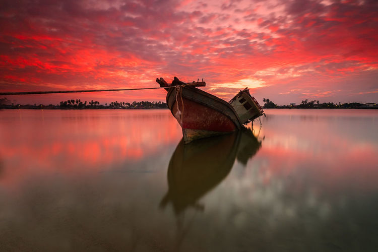 An old boat at the beach with the burning sky during sunset Beauty In Nature Cloud - Sky Fishing Boat Mode Of Transportation Moored Nature Nautical Vessel No People Non-urban Scene Orange Color Outdoors Reflection Scenics - Nature Sea Sinking Sky Sunset Tranquil Scene Tranquility Transportation Water
