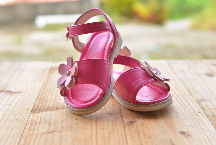 Close-up of pink sandals on wooden table