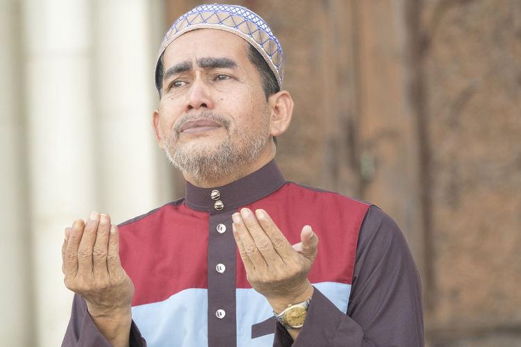 Close-Up Of Mature Man Praying While Sitting At Mosque
