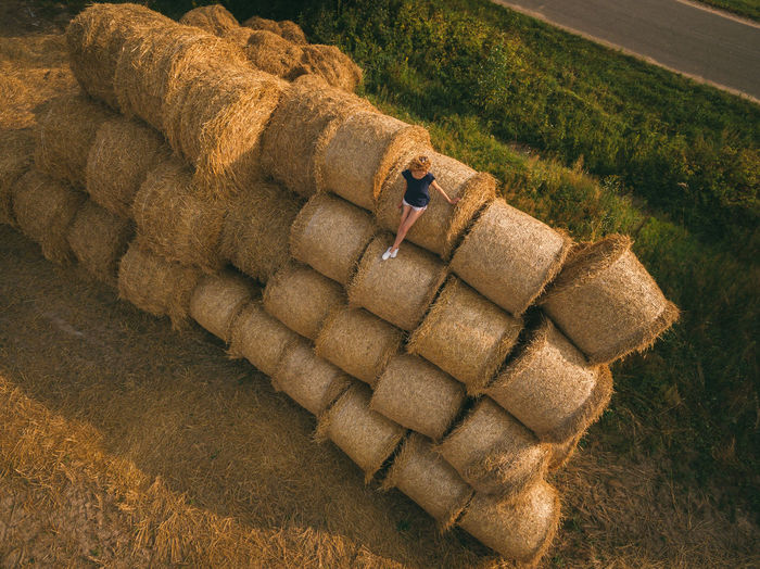 High angle view of woman sitting on hay stack