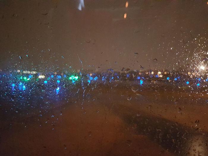 Illuminated Night Wet Water Rain Transparent Glass - Material No People Drop Window Lighting Equipment Nature Outdoors Motion City Transportation Light Rainy Season Nightlife RainDrop