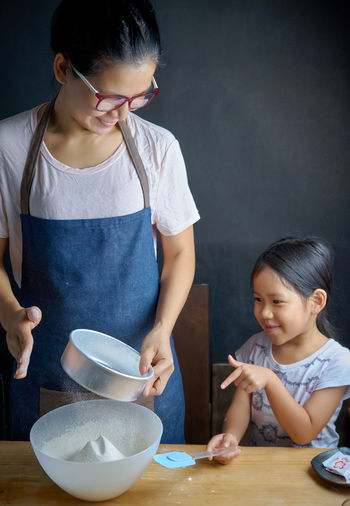 Daughter looking at mother straining flour in kitchen