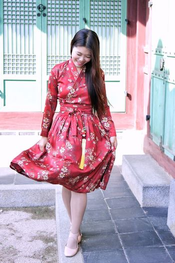 Full length of smiling young woman in floral dress walking outdoors