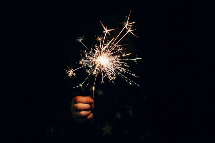 Person hand holding sparkler at night