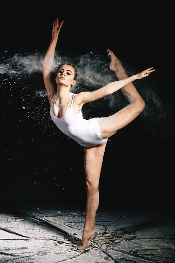 Young woman dancing against black background
