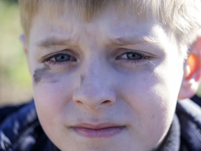 Close-Up Portrait Of Boy With Soot Smear On Face