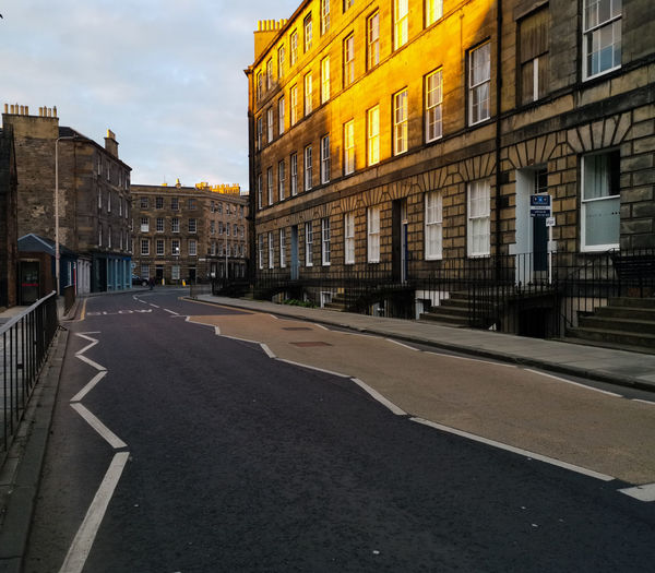 Empty road by buildings against sky in city