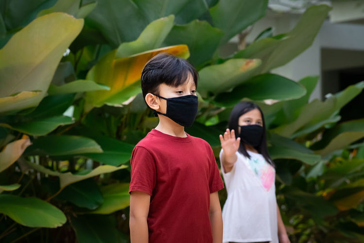 Two asian children wearing mask standing in distance of 1 meter from others keeping distancing.