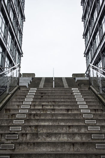 Low angle view of staircase amidst buildings against clear sky