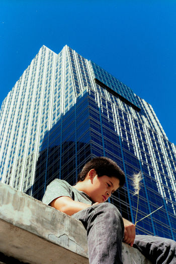 Low angle view of young man sitting on retaining wall against building during sunny day