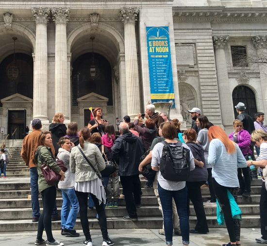 Woman Speaking To Tourists Against Historic Building