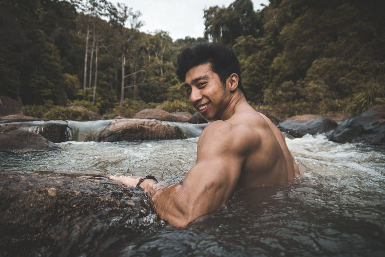 Portrait of smiling shirtless man in stream