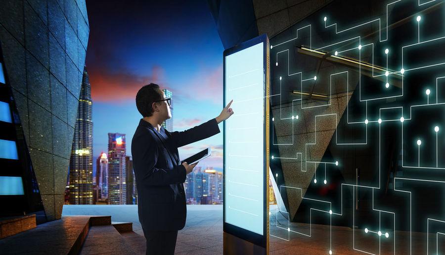 Digital composite image of businessman using large smart phone