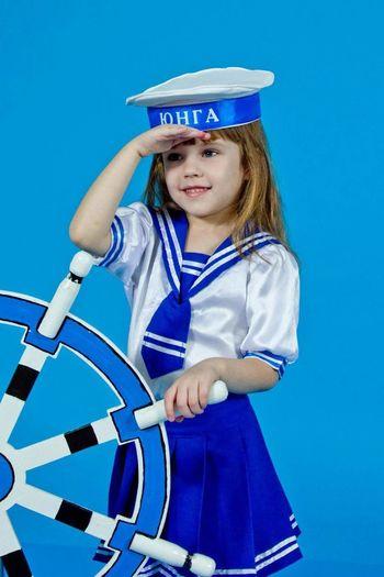 Cute girl wearing sailor uniform saluting against blue background