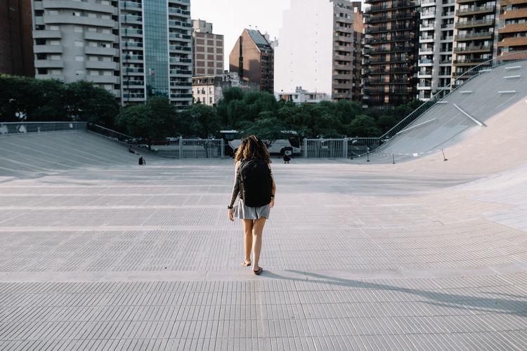 Rear view of woman walking on modern buildings in city