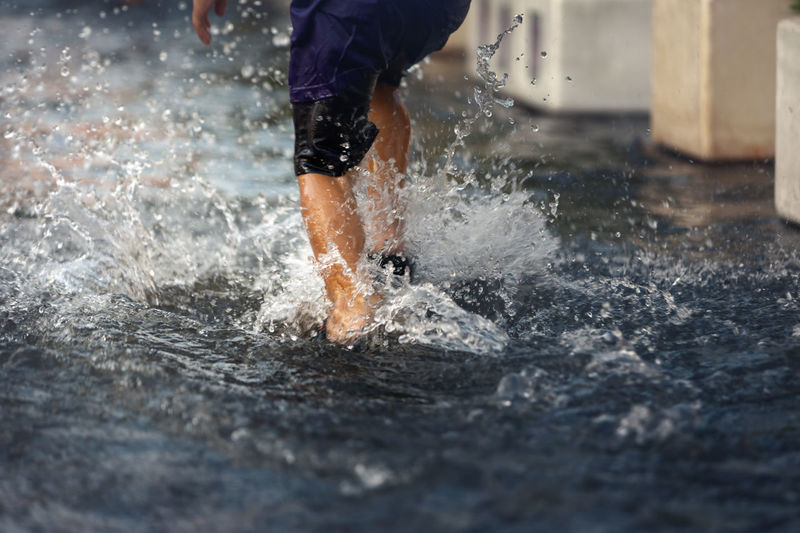 Low section of man splashing water in sea