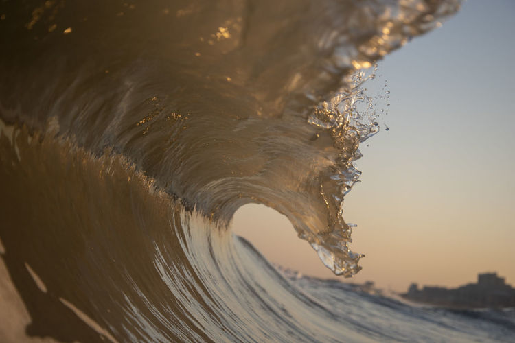 Sea waves splashing against clear sky during sunset