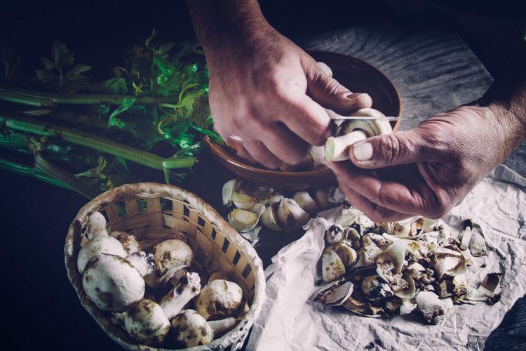 Cropped image of chef peeling mushroom on table