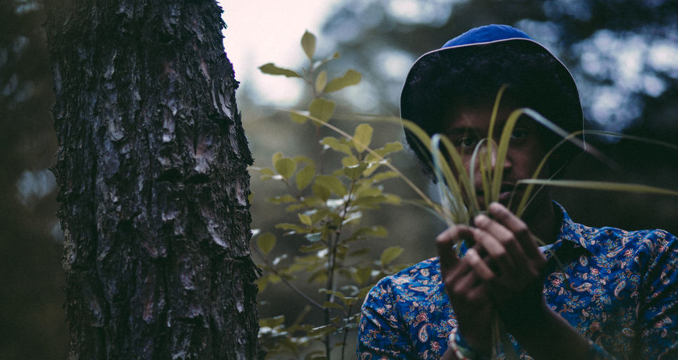 Man holding plants in forest