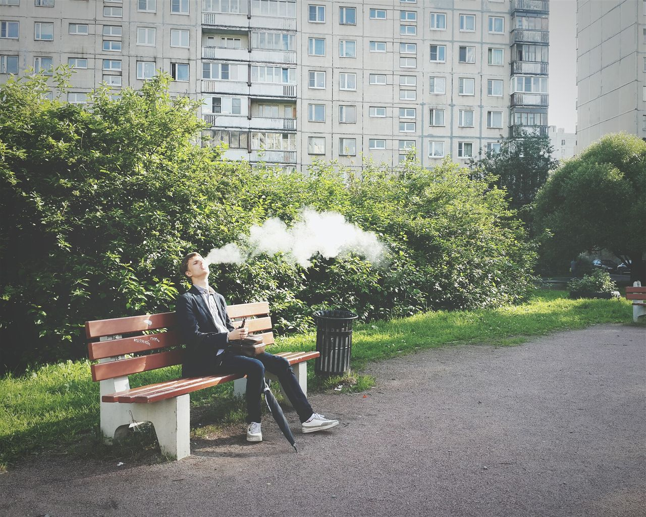 Young Man Smoking Sitting On Bench In Park