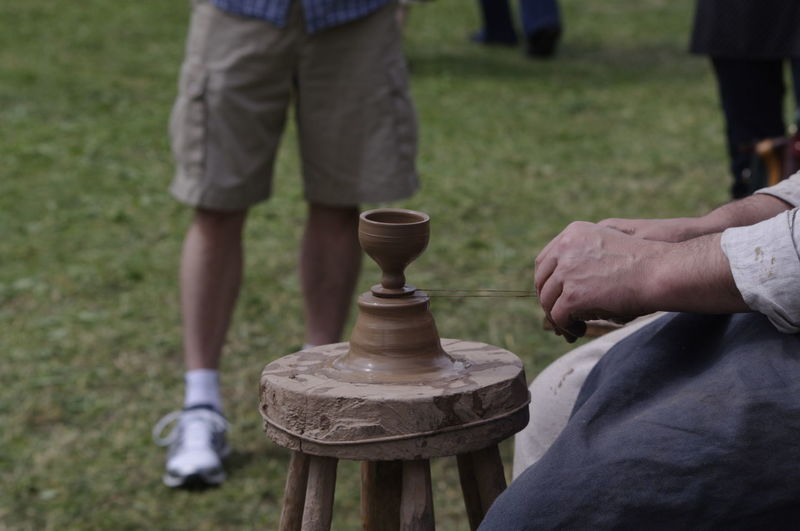 Midsection of man molding clay on stool at field