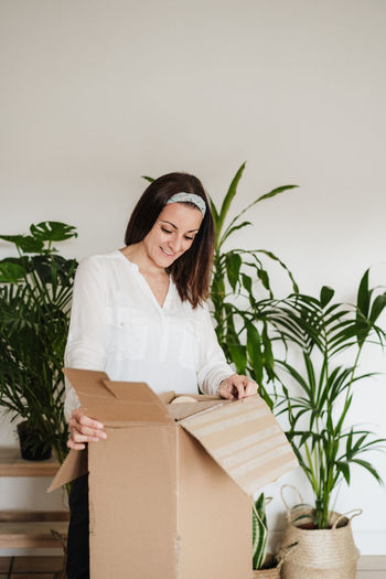 Young woman holding potted plant in box