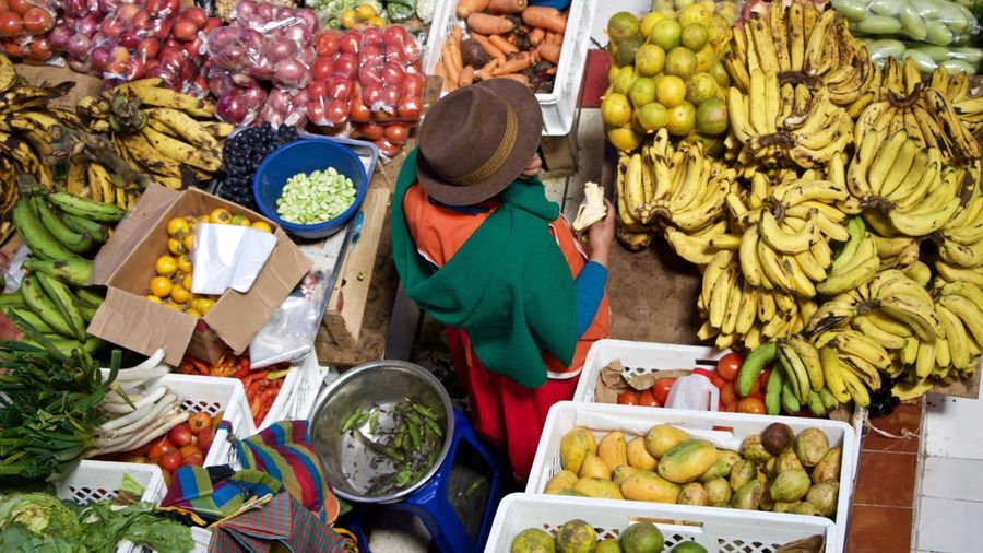 High angle view of woman buying fruits at market stall