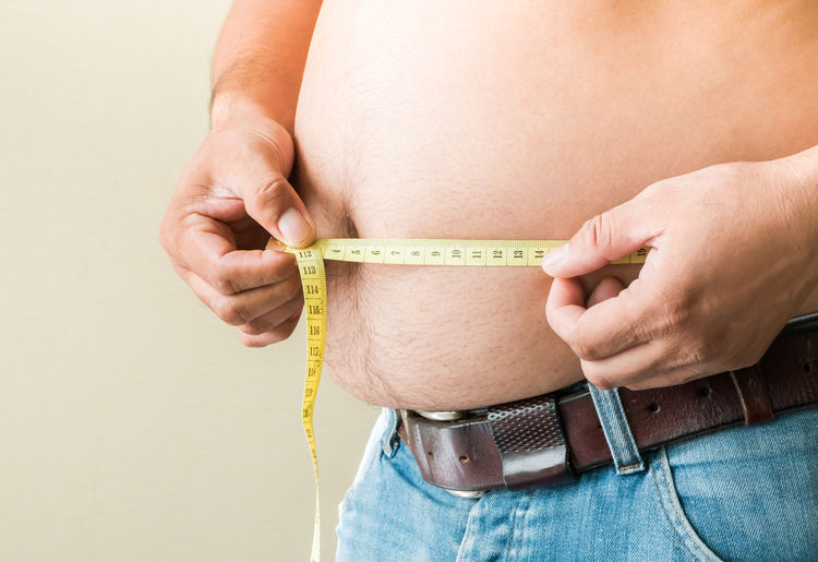 Midsection of man holding measuring tape against beige background
