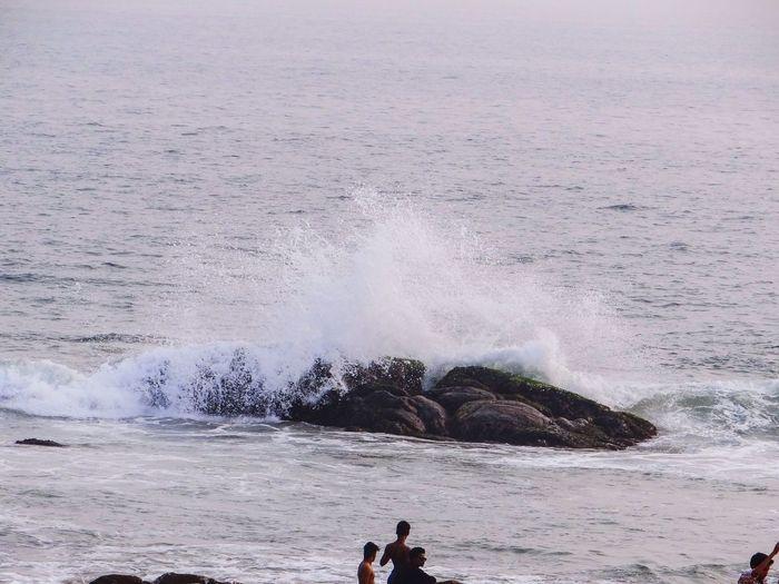 Men against wave in sea