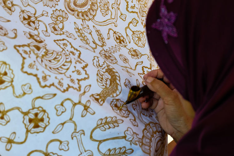 Close-up of woman making design on fabric