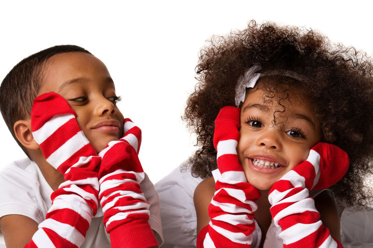 Close-Up Of Siblings Wearing Socks On Hands Against White Background