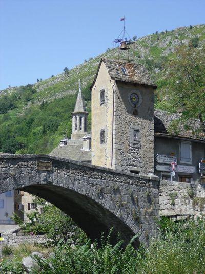 Old bridge amidst buildings against sky