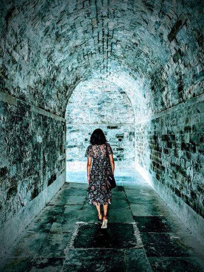 Rear view of woman walking in tunnel