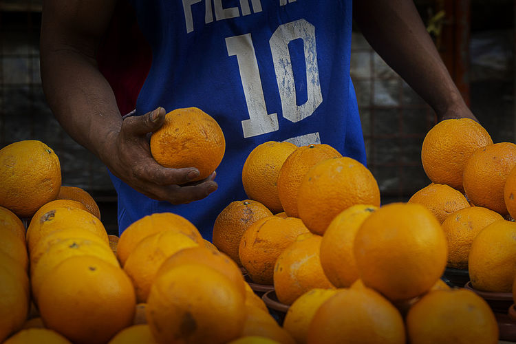 Midsection of vendor holding orange at street market stall