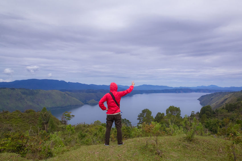 man standing on hill looking at the lake toba Field Freedom Retro Toba Tourist Travel Beauty In Nature Casual Clothing Cloud - Sky Day Forest Full Length Hand Raised Hiker Hill Lake Landscape Leisure Activity Lifestyles Meadow Men Mountain Mountain Range Nature One Person Outdoors People Real People Scenics Sky Standing Summer Tranquility Traveler Vintage